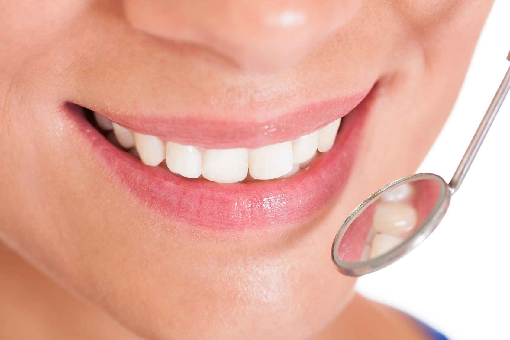 Smiling woman with perfect white teeth and a small dentists mirror reflecting her teeth being held alongside